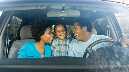 A smiling African American family inside a car.